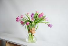 Bouquet de tulipes de fleurs dans le décanteur de cruche de café sur la table blanche en soleil Fond blanc Rose et bourgeons lila photo libre de droits
