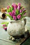 Bouquet de tulipes, oeufs de pâques et outils de jardin roses Image stock