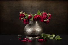 Bouquet of dead red roses in pewter vase, grunge background Stock Photos