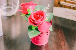 A bouquet of decorative pink roses stands in an iron pail on the table. Beautiful red flower bud. wooden table surface stock photos