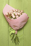 Bouquet of delicate pink roses on the small green wooden backgro Royalty Free Stock Photo