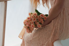 Bouquet of delicate pink spray roses on a background of pink lace dresses, girls hand. Bouquet of delicate pink spray roses on a background of pink lace dress Stock Photo