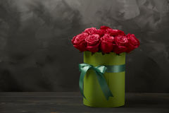 Bouquet of delicate red roses in green gift box on dark grey rustic background. Home decor. Bouquet of delicate red roses in green gift box on dark grey rustic Stock Photo