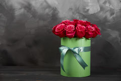 Bouquet of delicate red roses in green gift box on dark grey rustic background. Home decor. Bouquet of delicate red roses in green gift box on dark grey rustic Stock Photos