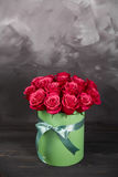 Bouquet of delicate red roses in green gift box on dark grey rustic background. Home decor. Bouquet of delicate red roses in green gift box on dark grey rustic Royalty Free Stock Photo