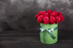 Bouquet of delicate red roses in green gift box on dark grey rustic background. Home decor. Bouquet of delicate red roses in green gift box on dark grey rustic Stock Photography