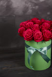 Bouquet of delicate red roses in green gift box on dark grey rustic background. Home decor. Bouquet of delicate red roses in green gift box on dark grey rustic Royalty Free Stock Photos