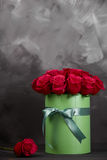 Bouquet of delicate red roses in green gift box on dark grey rustic background. Home decor. Bouquet of delicate red roses in green gift box on dark grey rustic Royalty Free Stock Photography