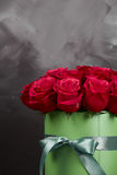 Bouquet of delicate red roses in green gift box on dark grey rustic background. Home decor. Bouquet of delicate red roses in green gift box on dark grey rustic Stock Images