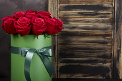 Bouquet of delicate red roses in green gift box on dark grey rustic wooden background. Home decor. Royalty Free Stock Photos
