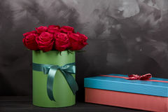 Bouquet of delicate red roses in green gift box on dark grey rustic wooden background. Home decor. Royalty Free Stock Photography