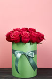 Bouquet of delicate red roses in green gift box on pink background. Home decor. Royalty Free Stock Photos