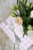 Bouquet of delicate tulips on the tablecloth and two forks. Bouquet of delicate pink tulips on the tablecloth and two forks Royalty Free Stock Images