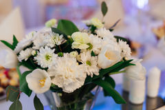 Bouquet of delightful white flowers stands on the table Stock Images