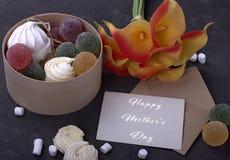 Bouquet des callas jaunes rouges avec la confiture d'oranges de guimauves dans une boîte ronde en bois et de l'enveloppe avec mar Photo stock