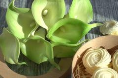 Bouquet des callas jaunes vertes avec des guimauves dans une boîte ronde en bois sur un fond en bois gris Photographie stock