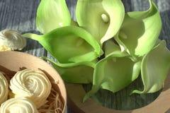 Bouquet des callas jaunes vertes avec des guimauves dans une boîte ronde en bois sur un fond en bois gris Photo stock