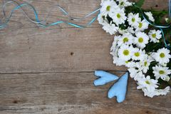 Bouquet des chrysanthèmes blancs avec l'enveloppe et de deux coeurs bleus sur le bois Images libres de droits
