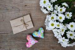 Bouquet des chrysanthèmes blancs avec l'enveloppe et de deux coeurs sur le bois Photos libres de droits