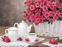 Bouquet des chrysanthèmes dans un thé de panier et de lait Concep rural photographie stock