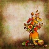 Bouquet des feuilles et des fleurs d'automne dans un vase d'un potiron sur un fond d'isolement Photographie stock