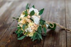 Bouquet des fleurs blanches, des creamflowers et des verts se trouvant sur un courtiser Photo stock