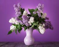 Bouquet des fleurs blanches et lilas dans le vase sur la table photos libres de droits