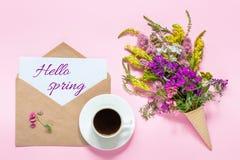 Bouquet des fleurs colorées dans le cône de gaufre, tasse de café et enveloppe avec le ressort des textes de carte bonjour sur la photo stock