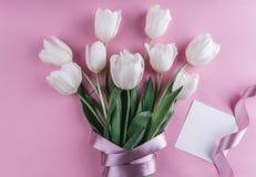 Bouquet des fleurs de tulipes et de la feuille de papier blanches au-dessus de fond rose-clair images stock