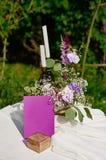 Bouquet des fleurs et de deux bougies sur la table pour une cérémonie de mariage en parc Images stock