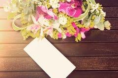 Bouquet des fleurs et de la carte blanche sur la table en bois avec le ligh chaud Images libres de droits