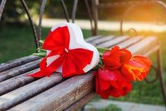 Bouquet des fleurs et du boîte-cadeau rouges de tulipe Photographie stock libre de droits