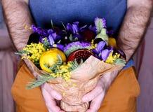 Bouquet des fleurs et du fruit dans des mains Photographie stock libre de droits