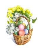 Bouquet des fleurs et du panier de Pâques avec les oeufs colorés Image stock