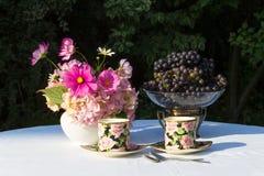 Bouquet des fleurs roses, des raisins et de deux tasses de porcelai anglais Photographie stock