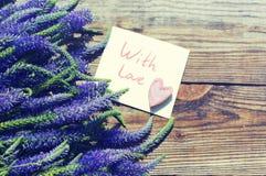 Bouquet des fleurs sauvages bleues d'été, d'un coeur décoratif et de la carte blanche avec l'inscription avec amour Photos libres de droits