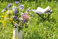 Bouquet des fleurs sauvages et d'un livre ouvert Images stock