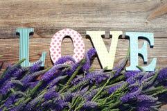 Bouquet des fleurs sauvages violettes d'été et le message sur l'amour des lettres lumineuses Photographie stock libre de droits