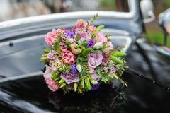 Bouquet des fleurs sur la rétro voiture de mariage de capot Photographie stock libre de droits