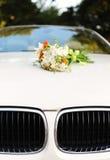 Bouquet des fleurs sur le capot de voiture photographie stock libre de droits