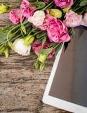 Bouquet des fleurs sur une table en bois avec un esprit de tablette Photos stock