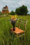 Bouquet des fleurs sur une vieille chaise dans la haute herbe Photographie stock