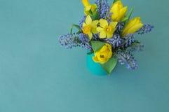 Bouquet des jonquilles, des tulipes et du Muscari Pâques Les oeufs de pâques sont bleus et turquoise Photographie stock libre de droits