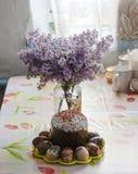 Bouquet des lilas près des gâteaux de Pâques et des oeufs colorés Images libres de droits