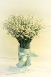 Bouquet des lis de la vallée dans un verre décoré d'une bande bleue avec un arc Photo libre de droits