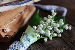 Bouquet des lis frais de la vallée et du rétro livre Photos stock