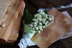 Bouquet des lis frais de la vallée et du rétro livre Photo stock