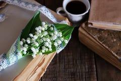 Bouquet des lis frais de la vallée et du rétro livre Images stock