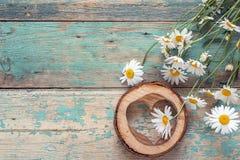 Bouquet des marguerites avec le coeur en bois sur le vieux fond en bois P Photo libre de droits
