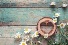 Bouquet des marguerites avec le coeur en bois sur le vieux fond en bois P Photographie stock libre de droits